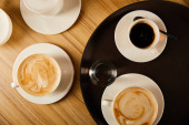 top view of cups of different coffee near glass of water on tray