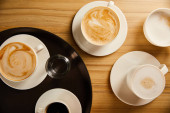 top view of cups of different coffee near glass of water on black tray