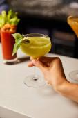 selektiver Fokus der Frau, die Margarita-Glas mit Cocktail berührt