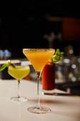 Selektiver Fokus auf gemixte kalte Cocktails in Gläsern an der Theke