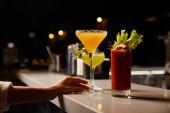 abgeschnittene Ansicht einer Frau, die Margaritaglas mit kaltem Cocktail auf der Theke berührt