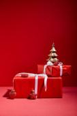 červené dárkové krabice a dekorativní zlatý vánoční stromek s ozdoby na červeném pozadí