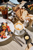 table with restaurant dishes and cheese pancakes with berries near cappuccino