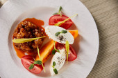 Fotografie vrchní pohled na lahodné jídlo restaurace s lilkem kaviárem a rajčaty