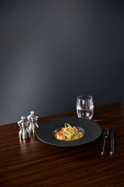 delicious restaurant soup with shrimps in black plate served on napkin with cutlery and water on black background