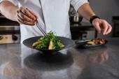 částečný pohled na kuchařské jídlo s rukolou, masem a bramborami v kuchyni v restauraci