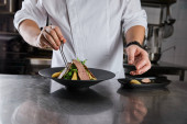 Fotografie partial view of chef making dish with arugula, meat and potato at kitchen in restaurant