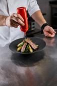 oříznutý pohled na kuchaře, jak nalévá omáčku na misku s rukolou, masem a bramborami v kuchyni v restauraci