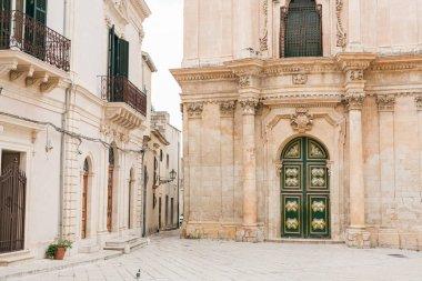 SCICLI, ITALY - OCTOBER 3, 2019: baroque facade of san michele arcangelo church  near buildings in Italy stock vector