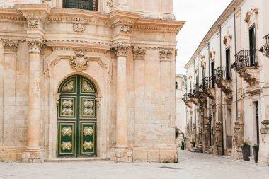 SCICLI, ITALY - OCTOBER 3, 2019: baroque facade of san michele arcangelo church near building with balconies in Italy stock vector