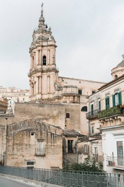 MODICA, ITALY - OCTOBER 3, 2019: baroque cathedral of san giorgio near old houses in sicily stock vector
