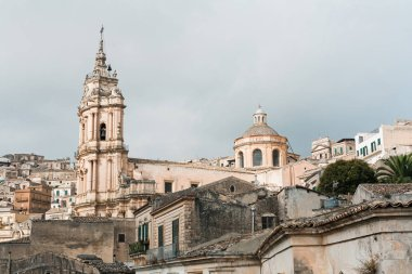 MODICA, ITALY - OCTOBER 3, 2019: baroque cathedral of san giorgio near houses against sky with clouds in sicily stock vector