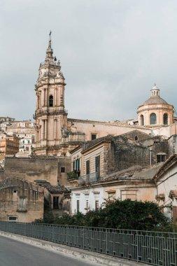 MODICA, ITALY - OCTOBER 3, 2019: baroque cathedral of san giorgio near houses in sicily stock vector