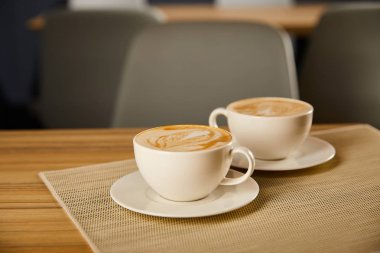 selective focus of creamy cappuccino in white cups on table