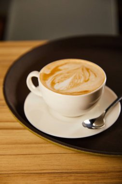 selective focus of cappuccino in white cup with saucer on black tray