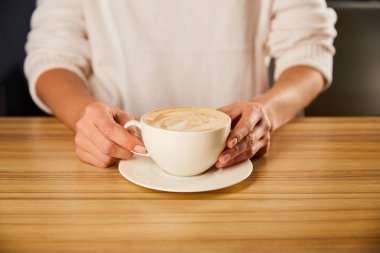 Cropped view of woman holding cup of cappuccino stock vector