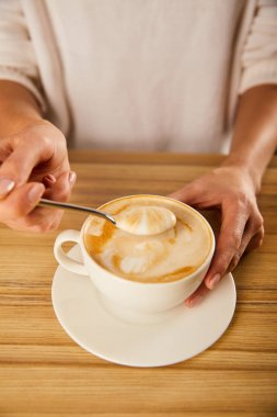 selective focus of woman holding spoon with cappuccino foam near wooden table