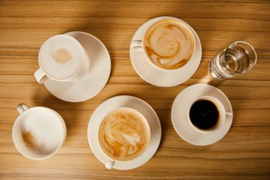 top view of saucers with cups of different coffee near glass of water