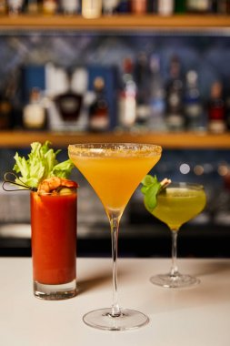 Selective focus of mixed and fresh cocktails in glasses on bar counter stock vector