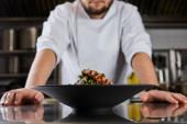 částečný pohled na kuchaře stojící u mísy s rukolou, masem a bramborami v kuchyni v restauraci