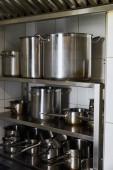 Metalltöpfe auf Gestell in Küche in Restaurant
