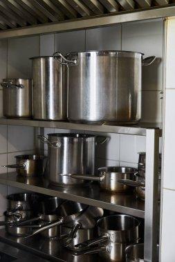 Metal pots on rack at kitchen in restaurant stock vector