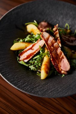 delicious warm salad with arugula, potato and meat in black plate on wooden table