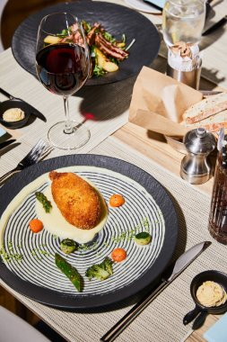 chicken kiev with mashed potato served on table with beverages in restaurant