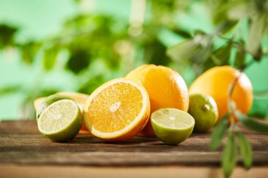 selective focus of cut, whole oranges and limes on wooden surface