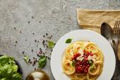 vrchní pohled na lahodné špagety s rajčatovou omáčkou na talíři poblíž listů bazalky a příbory na šedém texturovaném povrchu
