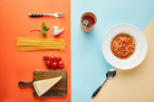 flat lay with delicious spaghetti with tomato sauce in plate near cutlery and ingredients on blue, red and yellow background