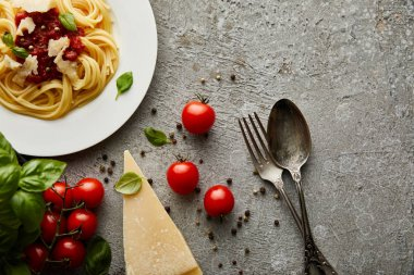 Top view of delicious spaghetti with tomato sauce on plate near cheese, tomatoes and cutlery on grey textured surface stock vector
