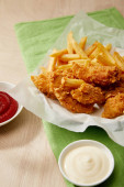 chicken nuggets with french fries, ketchup and mayonnaise on wooden table