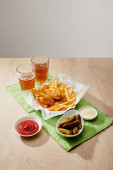 glasses of beer, chicken nuggets with french fries, sauces and gherkins on wooden table on grey background