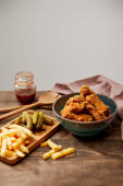 delicious chicken nuggets, french fries and gherkins on wooden table isolated on grey