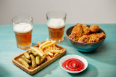 delicious chicken nuggets, ketchup, french fries and gherkins near glasses of beer on turquoise wooden table isolated on grey