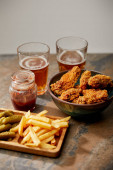 Fotografie delicious chicken nuggets, french fries and gherkins near glasses of beer on stone surface isolated on grey