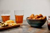 selektivní zaměření lahodných kuřecích nugetek, hranolek a okurek v blízkosti sklenic piva na kamenném povrchu izolovaném na šedé