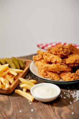 Selective focus of delicious chicken nuggets, mayonnaise, french fries and gherkins on wooden table with salt and rustic plaid napkin isolated on grey stock vector