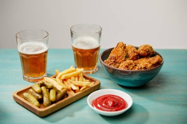 Delicious chicken nuggets, ketchup, french fries and gherkins near glasses of beer on turquoise wooden table isolated on grey stock vector
