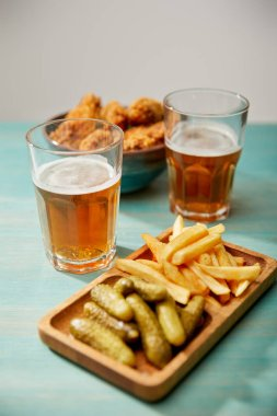 Selective focus of delicious chicken nuggets, french fries and gherkins near glasses of beer on turquoise wooden table on grey background stock vector