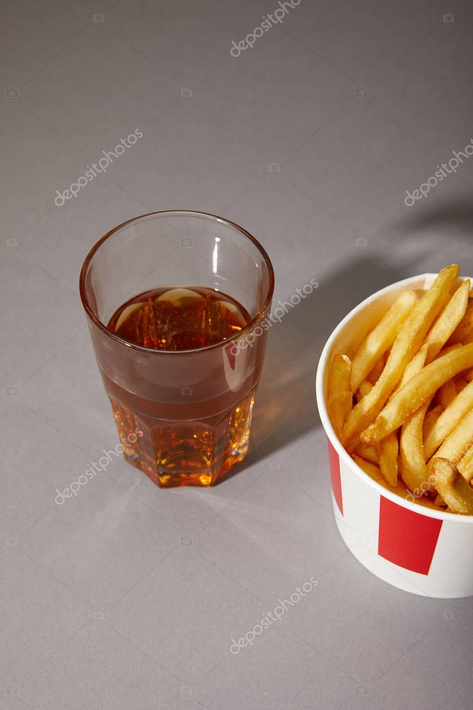Beer in glass near delicious french fries in bucket on grey background stock vector