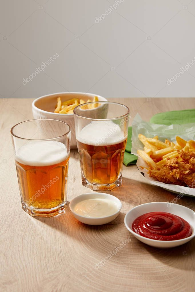 Glasses of beer, chicken nuggets with french fries, ketchup and mayonnaise on wooden table on grey background stock vector