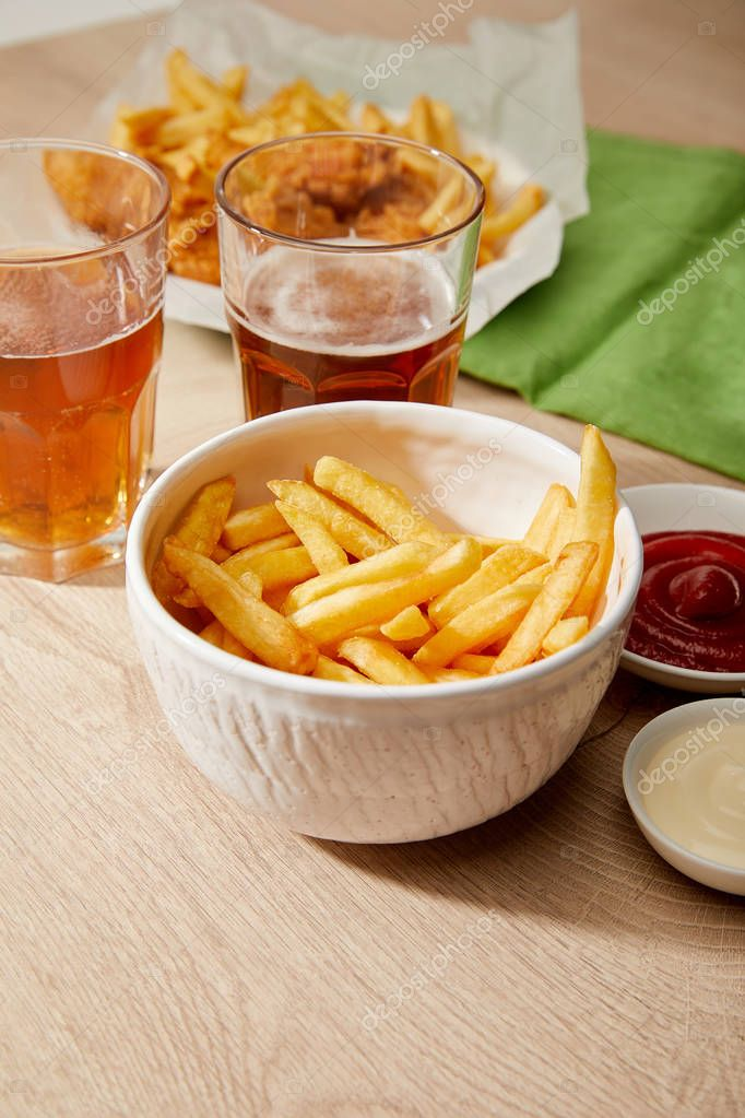 Glasses of beer, french fries in bowl, sauces on wooden table stock vector