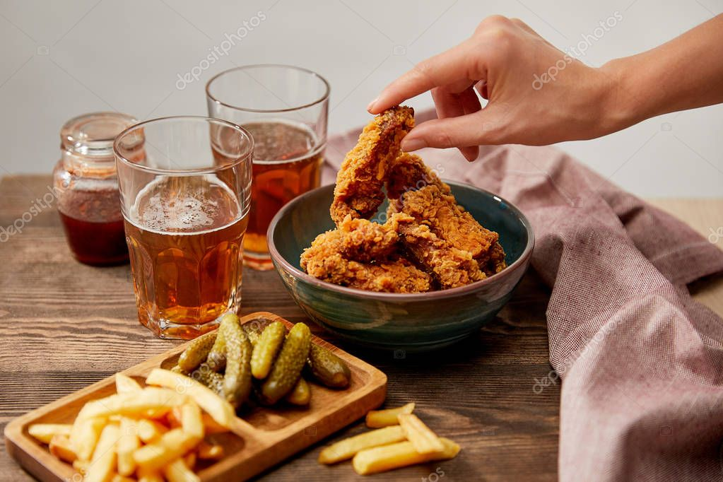 Cropped view of woman eating delicious chicken nuggets, french fries and gherkins near glasses of beer on wooden table isolated on grey stock vector