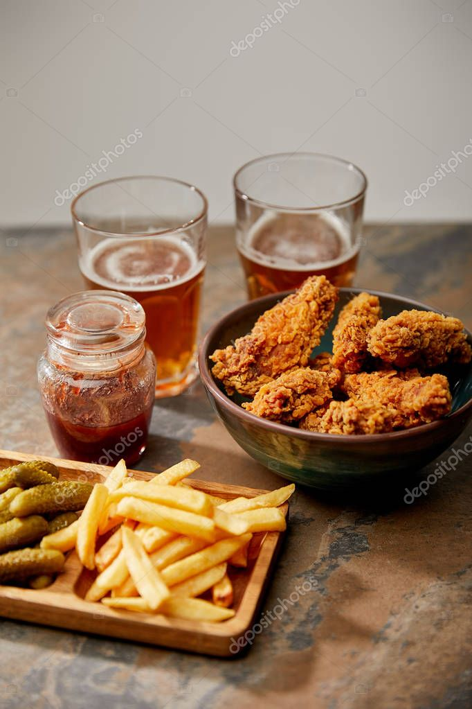 Delicious chicken nuggets, french fries and gherkins near glasses of beer on stone surface isolated on grey stock vector