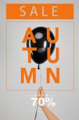 abgeschnittene Ansicht einer Frau mit schwarzem Ballon isoliert auf grau mit Herbstverkauf, bis zu 70 Prozent Illustration, Black-Friday-Konzept