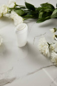 selective focus of roll on bottle of deodorant with flowers on white marble surface
