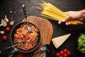 cropped view of man holding spaghetti near tasty bolognese pasta in frying pan on black background with fresh ingredients