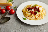 tasty bolognese pasta with tomato sauce and Parmesan on white plate near ingredients and cutlery on grey background